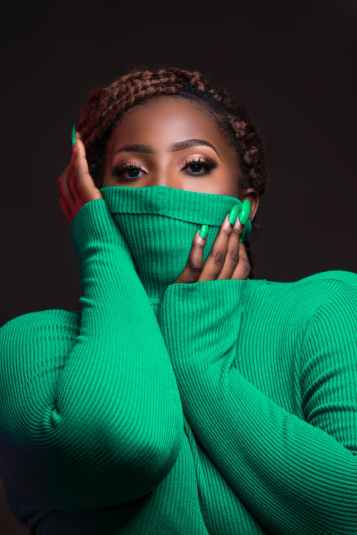 woman wearing green rib turtleneck sweater