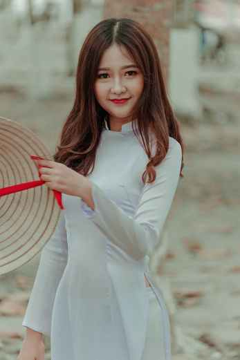 woman wearing white long sleeved dress holding straw hat
